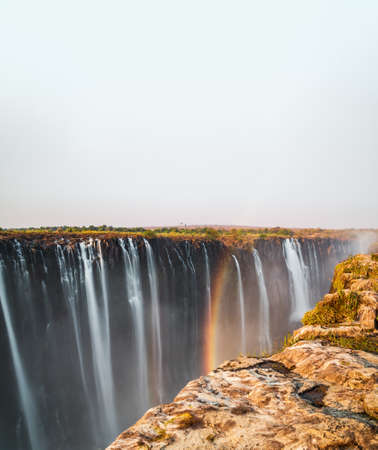 Victoria falls under white sky for text space with rainbow