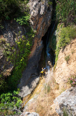 Unrecognizable person canyoning with ropes under the stream