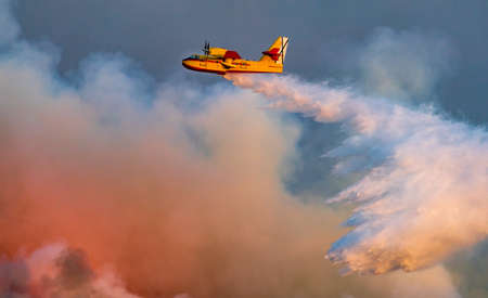 Profile view of hydroplane dropping water over huge fire Imagens