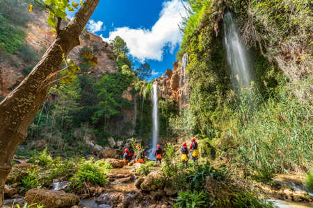 Large group of people enjoy waterfall descent using ropes