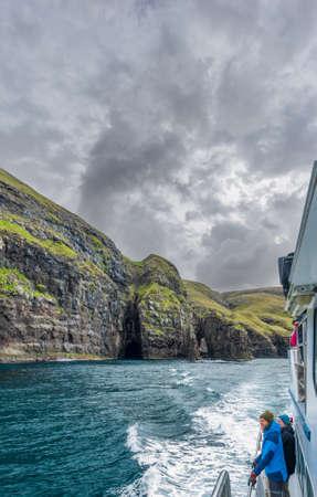 Blurred tourists over boat observing impressive Vestmanna cliffs