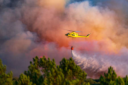 Smoke and helicopter dumping water with bambi-bucket