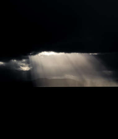 Dark clouds over the coastline and ocean with ray lights
