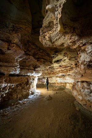 Unrecognizable person entering the cave with light