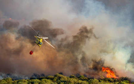Smoke and huge fire background and helicopter with bambi bucket