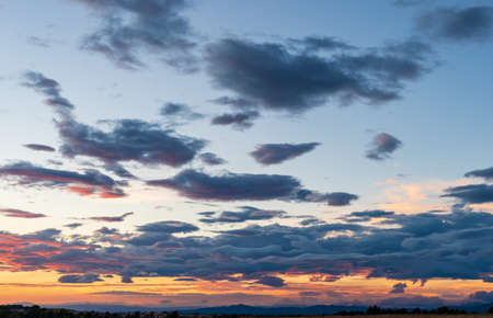 Sky background at sunset with blue clouds and mountain range