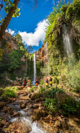Unrecognizable people enjoy waterfall descent using ropes Banque d'images