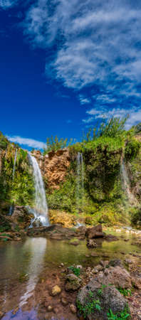 Vertical composition of waterfalls and blue sky for text space
