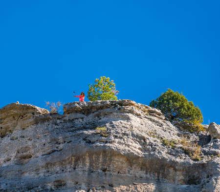 Unrecognizable tourist taking selfie over dangerous cliffs