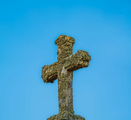 Antique old cross covered with moss against blue background Stock fotó