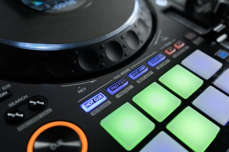 Close up DJ mixer player and sound console for house music party. DJ controller for mixing music and colorful light in nightclub. Disc jockey panel and mixing deck at dance party 写真素材
