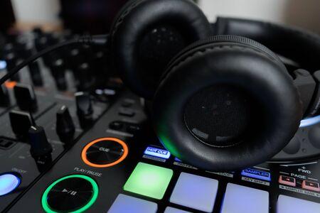 Professional dj headphones on audio mixer controller.Big black headset on sound mixing panel.Audio equipment for disc jockey Stockfoto
