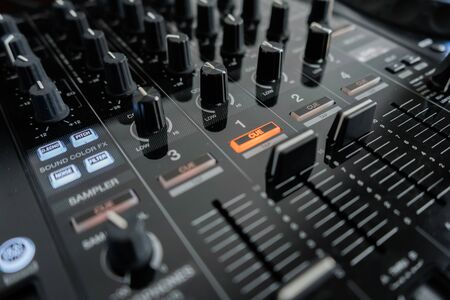 Wide angle photo of black sound mixer controller with knobs and sliders
