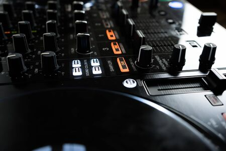 Wide angle photo of black sound mixer controller with knobs and sliders Stock Photo
