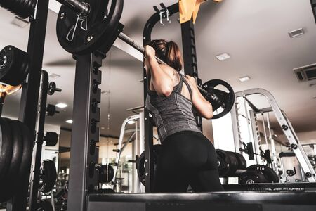 Young beautiful girl in the gym doing exercises on the squat with a barbell, improving the muscles of the buttocks and legs.