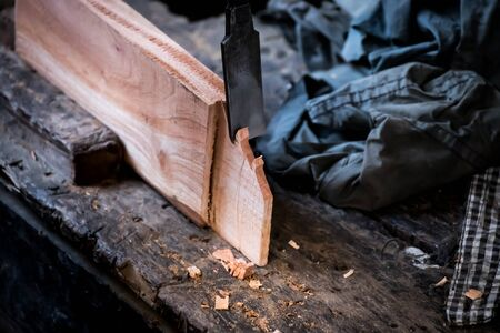 Hands of carpenter with chisel in the hands on the workbench in carpentry Banco de Imagens