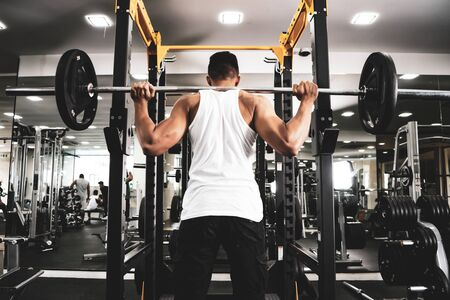 Man at the gym. Execute exercise squatting with weight, in gym Фото со стока