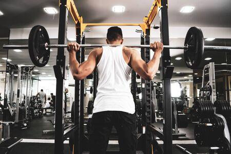 Mann im Fitnessstudio. Führen Sie Kniebeugen mit Gewichten im Fitnessstudio durch Standard-Bild