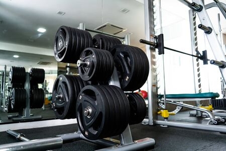 Modern light gym. Sports equipment in gym. Barbells of different weight on rack. 스톡 콘텐츠