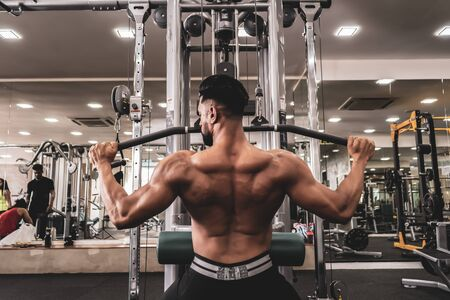 Fit man on lat pulldown machine at the health club. Work out on Pulldown Weight Machine Stok Fotoğraf - 130835952