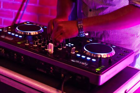 DJ playing music.Midi controller turntable.New digital technology for mixing audio tracks.Sound mixer with turntables.Disc jockey mix music at party on summer festival
