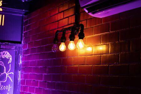 Burning light bulbs near bookshelf