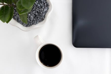 White office desk with coffee, office plant, laptop close. Top view with copy space, flat lay