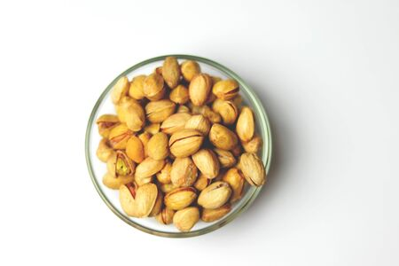 Dried pistachio nuts in class with white background