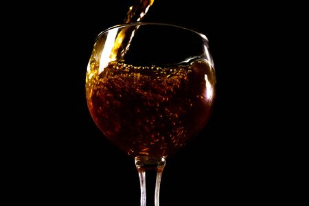 Red wine pouring into a glass close-up .Flowing wine from bottle
