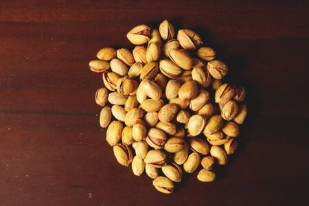 Dried pistachio nuts in class with brown background