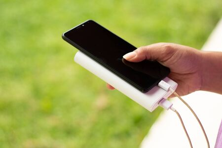 girl hold the phone outside with power bank, green grass
