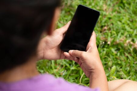 girl hold the phone single hands outside, green grass