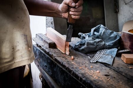 Hands of carpenter with chisel in the hands on the workbench in carpentry Stok Fotoğraf