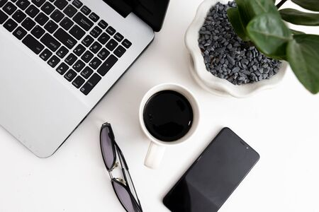 Workplace laptop and cup of coffee, office plant, sunglass, smartphone on a white background. Copyspace