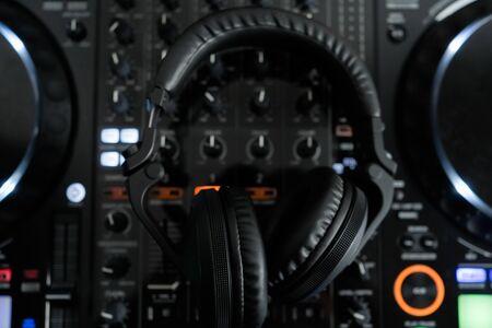 Professional dj headphones on audio mixer controller.Big black headset on sound mixing panel.Audio equipment for disc jockey Banque d'images