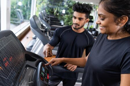 Well qualified trainer explains to his client how to use treadmill, wearing black t shirt and red sports jacket. Beautiful brunette lady follows all instructions, being concentrated and attentive.