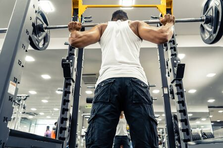 Man at the gym. Execute exercise squatting with weight, in gym Stok Fotoğraf