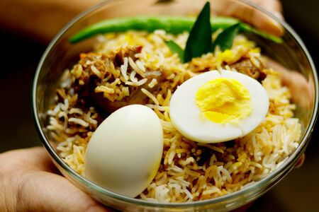 Delicious chicken biriyani hold with hand