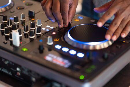 club dj plays music on stage in nightclub.Hand of disc jockey adjusting sound track volume level.Professional audio equipment on music festival
