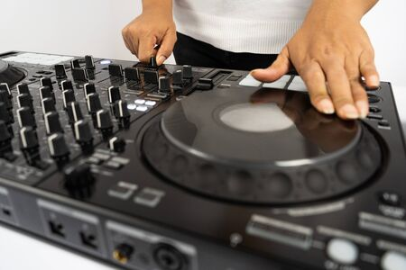 Hands of DJ mixing tracks on professional Dj Mixer