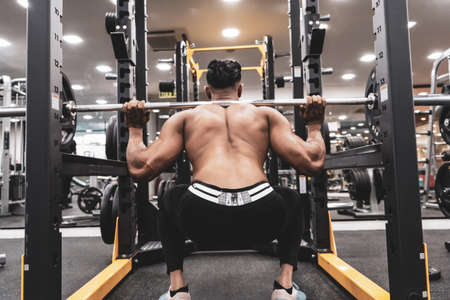 Man at the gym. Execute exercise squatting with weight, in gym Stock fotó