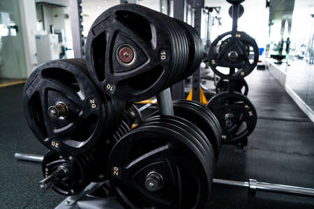 Modern light gym. Sports equipment in gym. Barbells of different weight on rack. Stock Photo