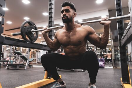 Man at the gym. Execute exercise squatting with weight, in gym Stock Photo