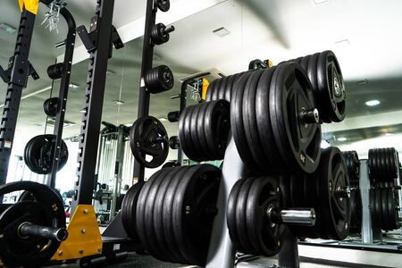 Modern light gym. Sports equipment in gym. Barbells of different weight on rack. Imagens