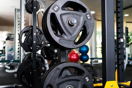 Modern light gym. Sports equipment in gym. Barbells of different weight on rack. 写真素材
