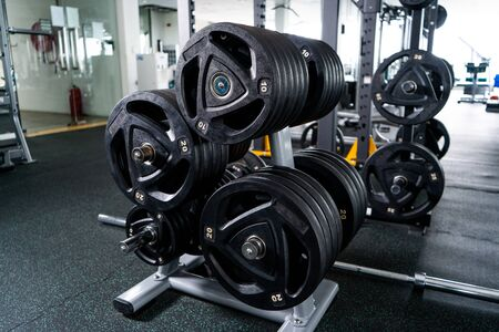 Barbells of different weight on rack.