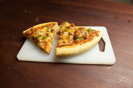 Pan Pizza slice on tray with dark brown wood top closeup