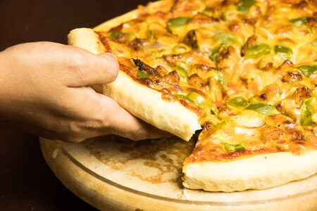 Pan Pizza slice take from hand side view with dark brown wood 写真素材