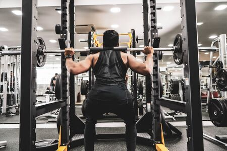 Man at the gym. Execute exercise squatting with weight, in gym Reklamní fotografie