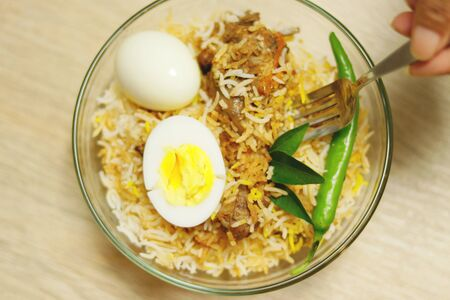 Delicious chicken biriyani hold with spoon